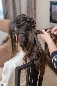 Hairdresser makes hairstyle bride