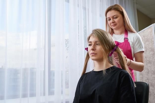 Парикмахер делает прическу девушке с длинными волосами в салоне красоты. создаем локоны с помощью щипцов для завивки
