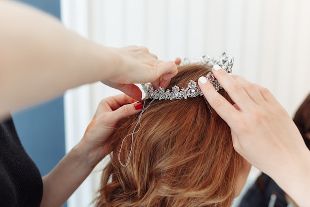 Hairdresser makes models hairstyle for bride, putting on tiara crown.