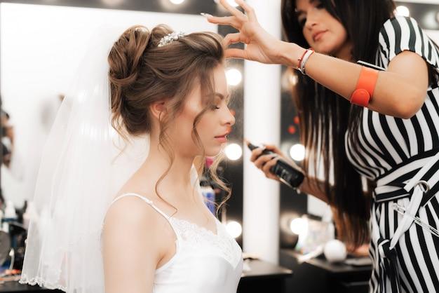 美容師はスプレーを使用して美しい女の子の花嫁をスタイリングします
