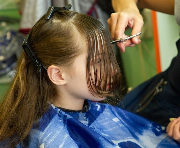 Парикмахер делает прическу милой маленькой девочке. девушка срезает челку. работа парикмахером.