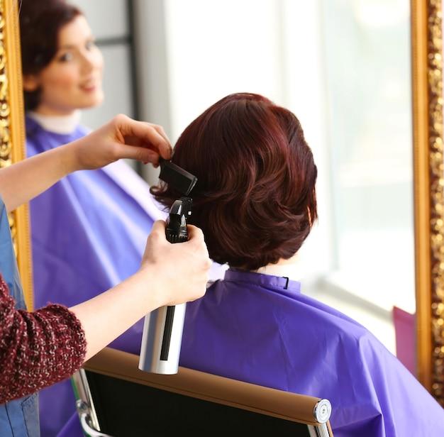 Парикмахер делает красивую стрижку молодой женщине в салоне красоты