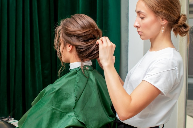 Hairdresser making hairstyle for woman.