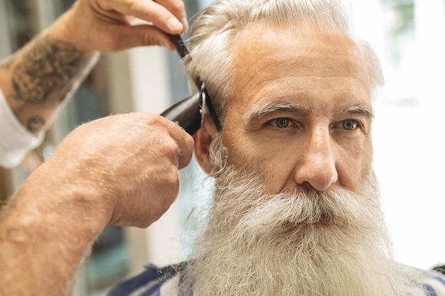 이발소에서 잘 생긴 노인을 위해 세련된 헤어 스타일을 만드는 미용사