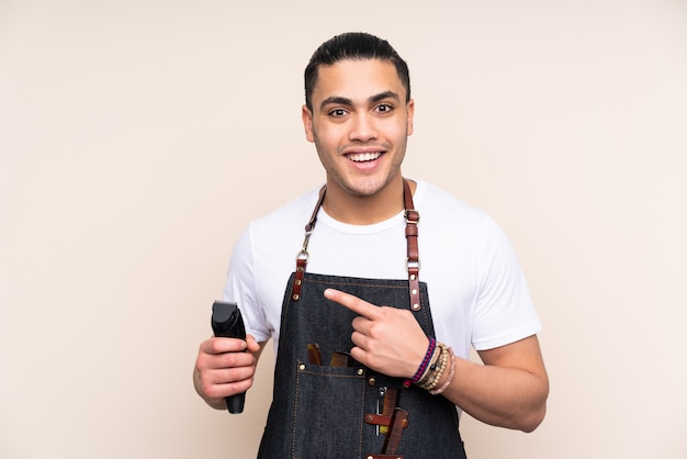 Hairdresser man in an apron isolated on beige wall pointing finger to the side