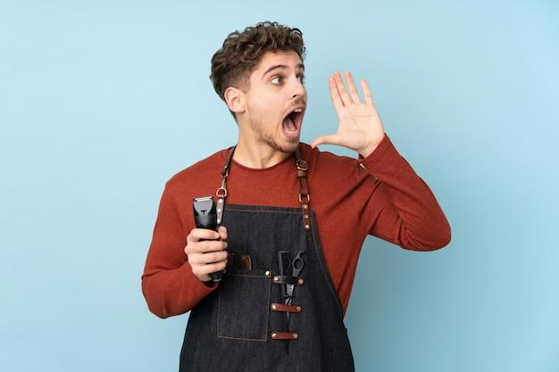 Человек парикмахера изолированный на голубой стене крича с широко открытым ртом