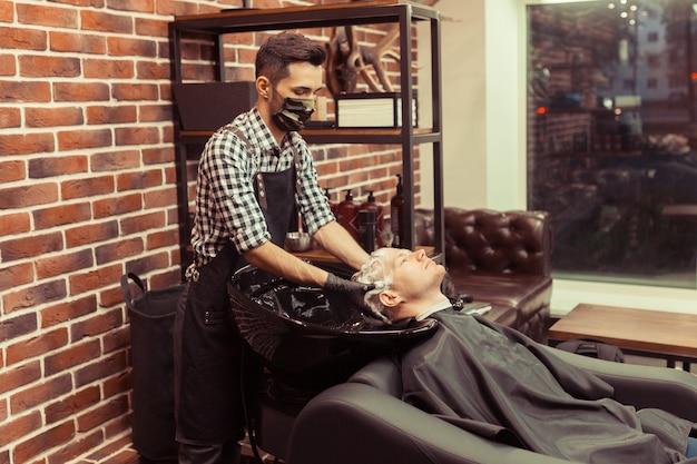 美容師の男がヴィンテージ理髪店でクライアントの頭を洗う