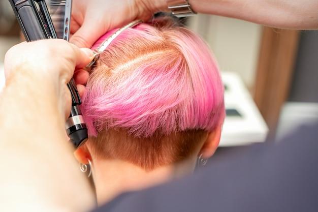 Парикмахер зажимает волосы зажимом