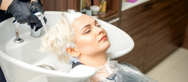 Hairdresser prepare to washes off the white dye from hair of young caucasian woman in sink at beauty salon