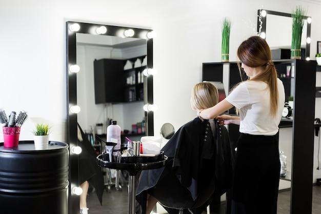 美容師は、クライアントの女性が手順を復元する準備をします