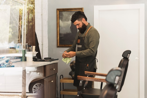 Hairdresser preparing equipment for work in barber shop