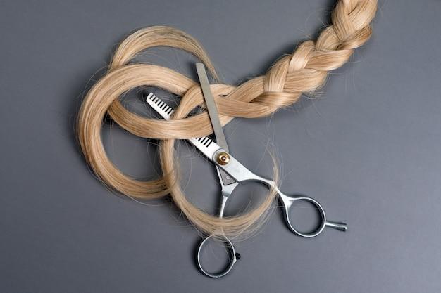 灰色の背景にブロンドの髪の三つ編みのストランドを持つ美容師のプロの間伐はさみまたは鋏。ビューティーサロン。灰色のテーブル、上面図のヘアエクステンションと理髪ツール。