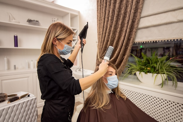 Hairdresser in protective mask drying the client's blond hair with a hairdryer