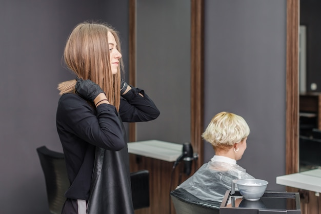 The hairdresser puts on black apron in the hair salon.