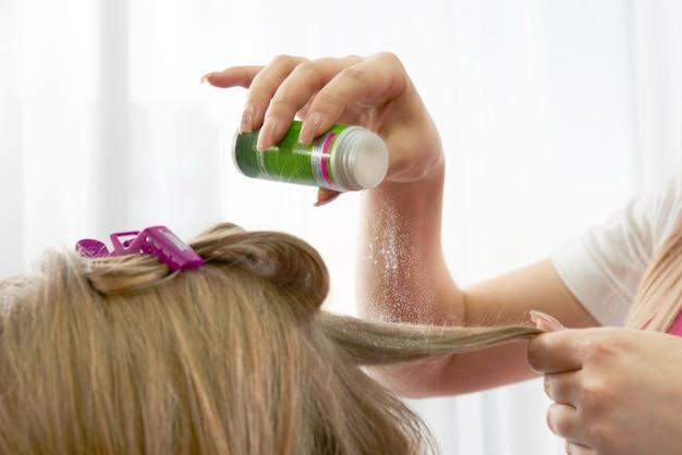 美容師はクライアントの髪にボリュームのパウダーを置きます