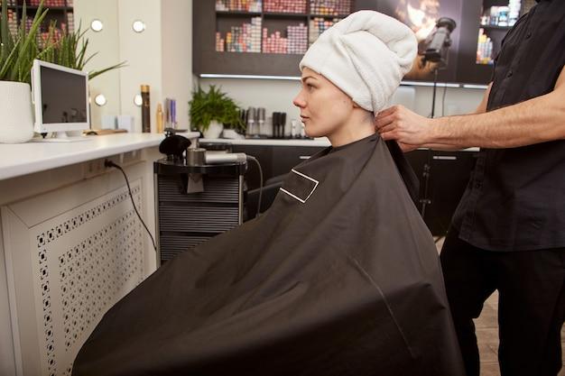 Парикмахер надевает парикмахерскую накидку на клиента в салоне красоты
