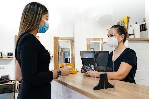 미용사의 고객이 미용사에게 비용을 지불합니다. 둘 다 코로나 바이러스로 인해 얼굴에 마스크가 있습니다. 둘 다 매우 행복합니다