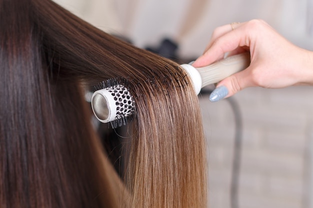 Hairdresser's hand brushing long brunette hair in beauty salon