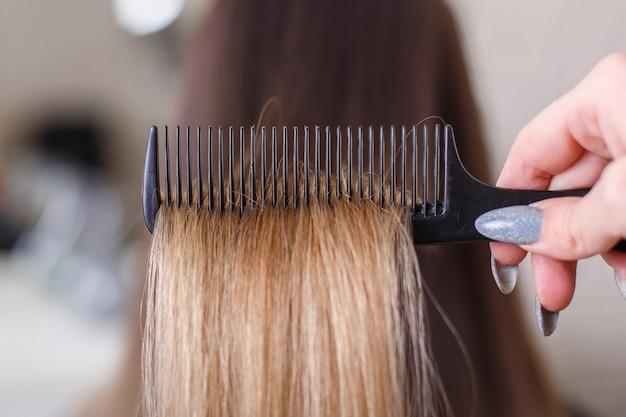 Рука парикмахера расчесывает длинные волосы брюнетки в салоне красоты Premium Фотографии
