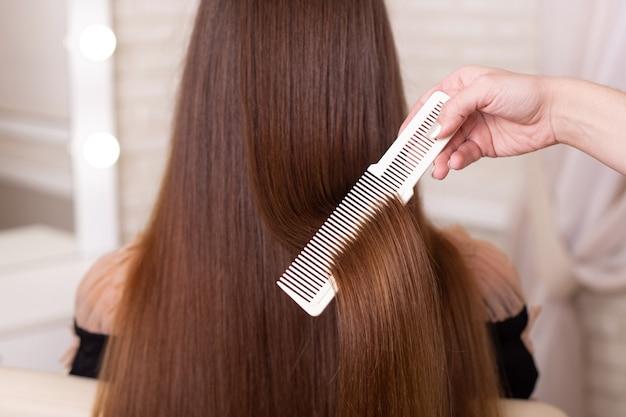 Рука парикмахера, расчесывающая длинные волосы брюнетки в салоне красоты