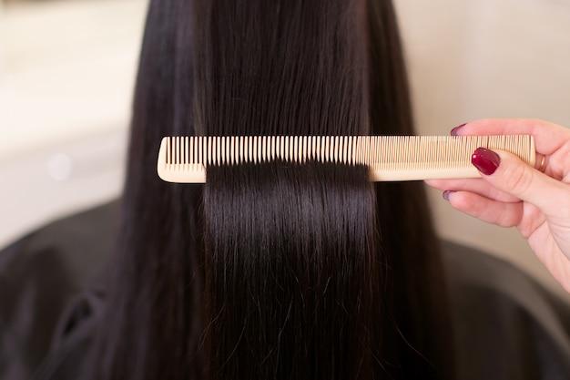 Рука парикмахера расчесывает длинные волосы брюнетки в салоне красоты