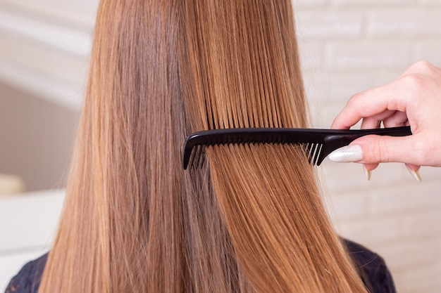 Hairdresser's hand brushing long brunette hair