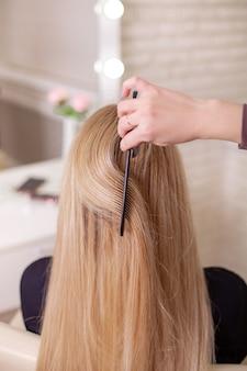 Рука парикмахера расчесывает длинные натуральные светлые волосы в салоне красоты