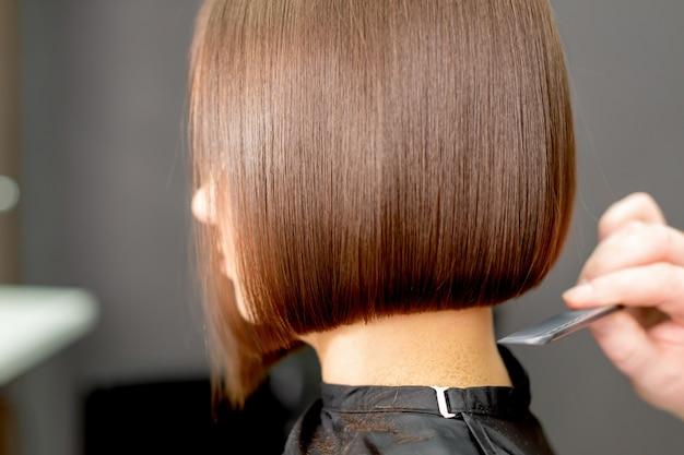 Парикмахерская рука расчесывает волосы женщины