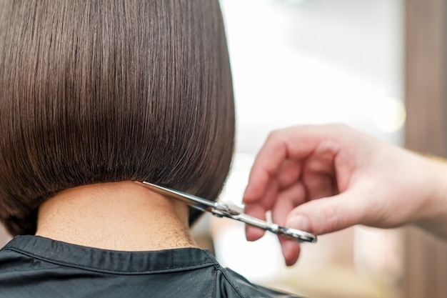 Hairdresser's hand cuting hair tips.
