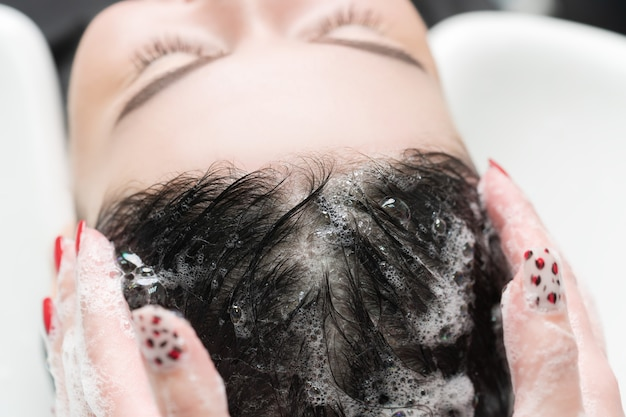 Hairdresser's hands wash long hair of brunette woman with shampoo in special sink for shampooing in beauty salon.