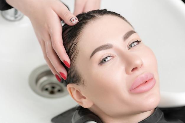 Руки парикмахера моют длинные волосы красивой брюнетки шампунем в специальной раковине для мытья головы в салоне красоты и прически.