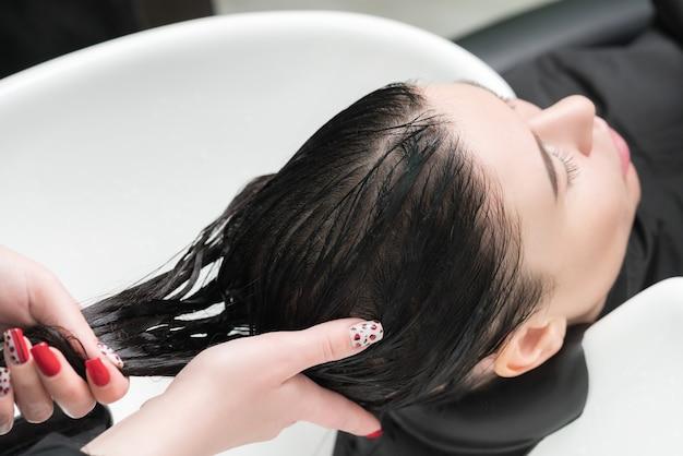 미용사의 손은 미용실에서 샴푸를 하기 위해 특수 세면대에 샴푸를 넣은 갈색 머리 여성의 긴 머리를 씻습니다.