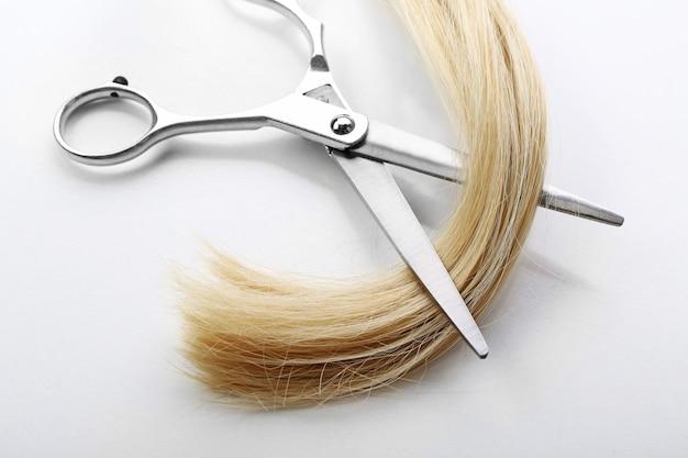 白で隔離されるブロンドの髪の束を持つ美容師のはさみ