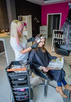 잡지를 읽는 동안 아름다운 젊은 여성에게 알루미늄 호일로 머리카락을 분리하는 미용사