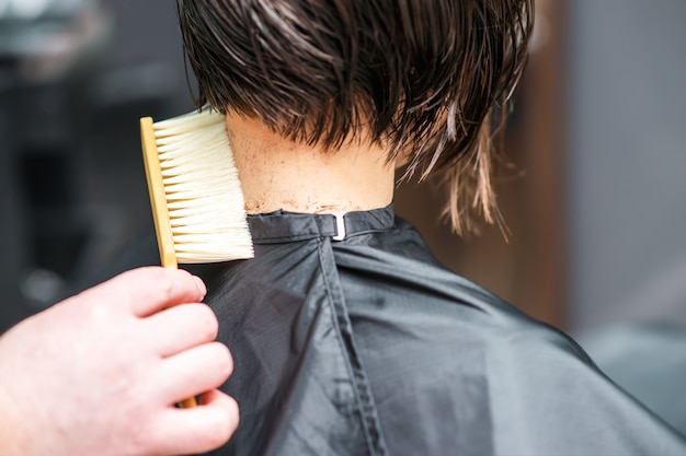Hairdresser shakes cut hair from neck of woman at hair salon.