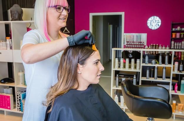 그녀의 머리 색깔을 변경하기 전에 아름다운 젊은 여성에게 머리 염색 샘플을 보여주는 미용사 프리미엄 사진
