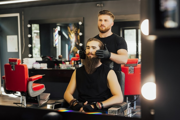 Парикмахер показывает свою работу в зеркале и стрижка удовлетворена удовлетворением клиентов