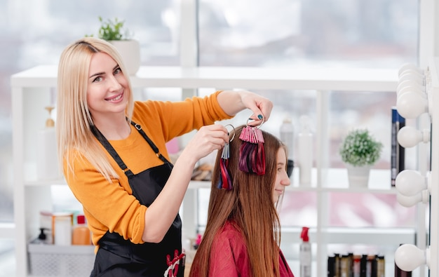 Hairdresser shows colorful samples for hair dyeing to beautiful model girl client and smiling