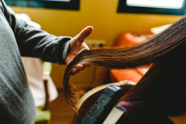 Hairdresser smoothing the dark hair of a client.