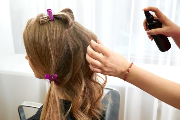 Hairdresser spray hair of young woman in beauty salon