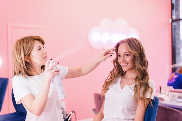 サロンで顧客の髪をスプレーする美容師