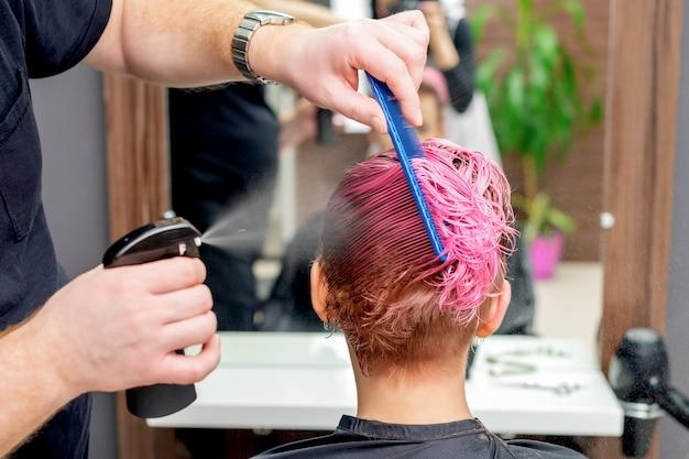 Hairdresser sprinkles water on hair.
