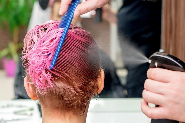 Парикмахер брызгает водой на розовые волосы женщины крупным планом.
