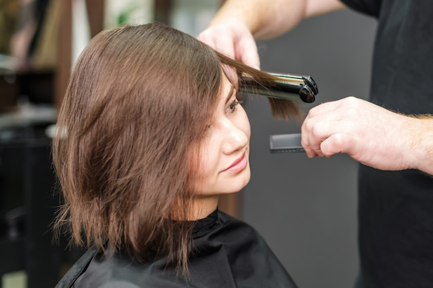 ヘアーアイアンで茶色の髪を矯正する美容師。