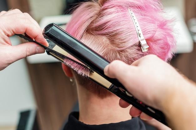 ヘアーアイアンでピンクの髪を矯正する美容師。