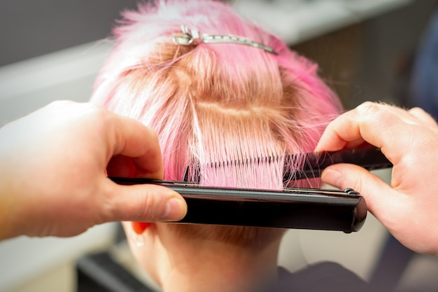 Hairdresser straightening short pink hair