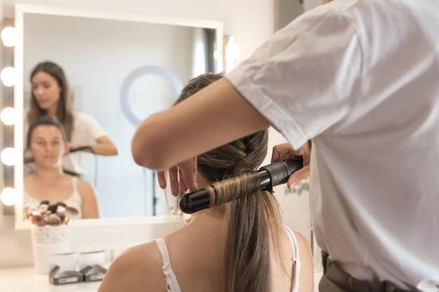 クライアントにフラットアイロンで髪をまっすぐにする美容師。理髪セッション。