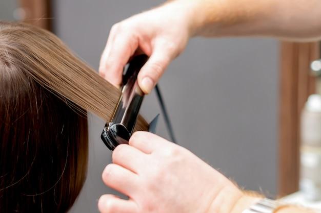 美容師は女性の髪を整えます。