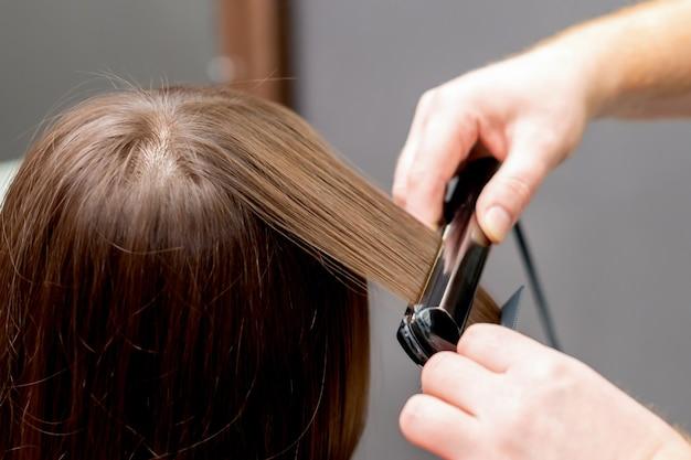 美容師は美容院でストレートヘアアイロンツールで女性の髪をまっすぐにします