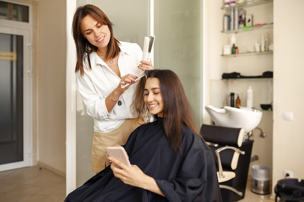 Hairdresser straightens woman's hair, hairdressing salon. stylist and client in hairsalon. beauty business, professional service
